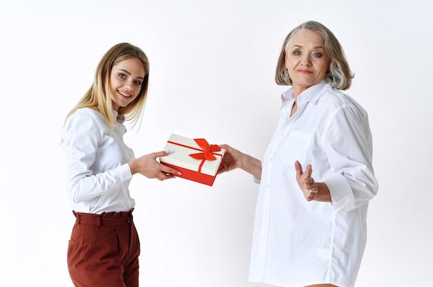 Mama i córka stoją obok prezentu świąteczne emocje
