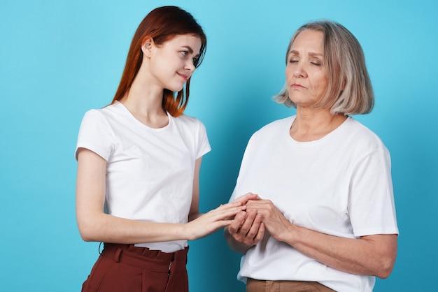Mama i córka trzymają się razem w białych koszulkach z rodziną