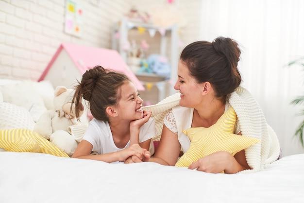 Mama i córka uśmiechają się i przytulają, leżąc na łóżku