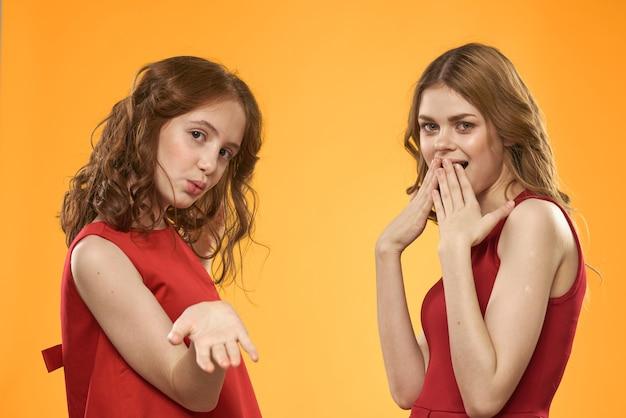 Mama i córka w czerwonych sukienkach komunikacja emocje styl życia żółte tło