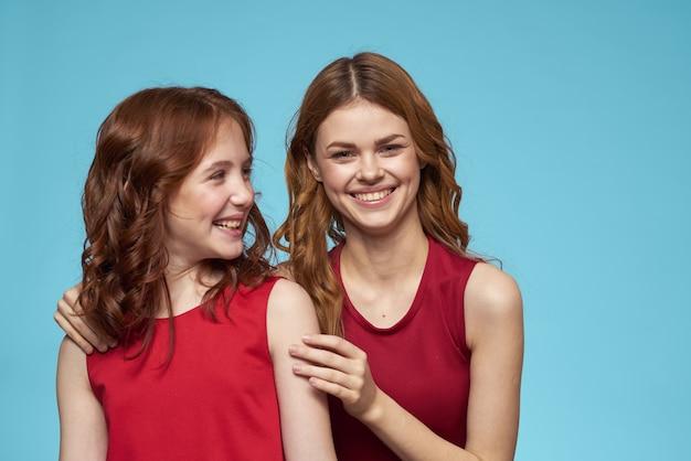 Mama i córka w czerwonych sukienkach rozrywka styl życia zabawa studio niebieskie tło