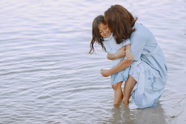 Mama i córka w identycznych sukienkach. rodzina bawić się nad rzeką.