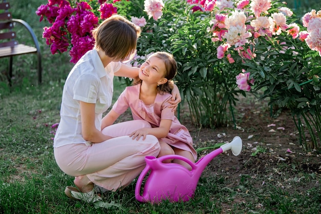 Mama i córka w lnianej różowej sukience dbają o piwonie w ogrodzie, podlewają kwiaty. doskonale się uśmiecha i śmieje. oświetlone promieniami zachodzącego wieczorem słońca.