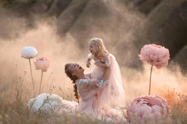 Mama i córka w różowych bajkowych sukienkach bawią się na polu otoczonym dużymi różowymi dekoracyjnymi kwiatami