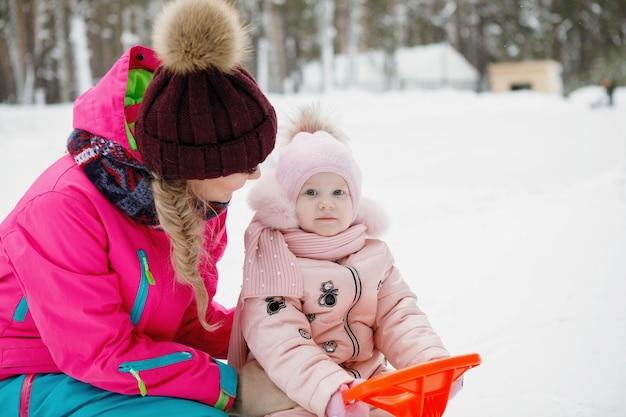 Mama i córka w śnieżnym parku zimą na świeżym powietrzu.