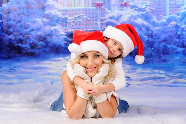 Mama i córka w świątecznych czapkach leżą na śniegu.