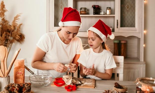 Mama i córka w świątecznych czapkach siedzą przy stole w kuchni i robią ciasteczka z ciasta