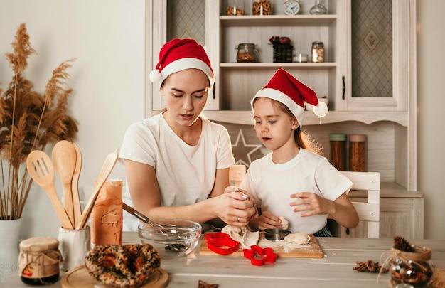 Mama i córka w świątecznych czapkach siedzą w kuchni i robią ciasteczka z ciasta