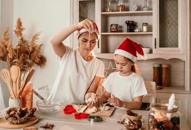 Mama i córka w świątecznych czapkach uczą się gotować ciasteczka w kuchni