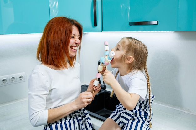 Mama i córka w turkusowej kuchni bawią się piankami. cudowne relacje rodzinne. szczęśliwa koncepcja rodziny