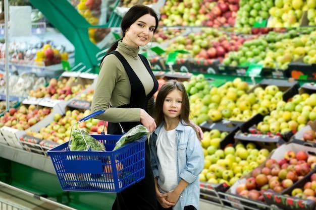 Mama i córka wybierają warzywa i owoce w supermarkecie.