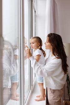 Mama i córka wyglądają przez okno domu