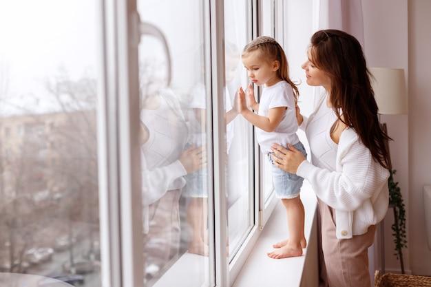 Mama i córka wyglądają przez okno na zewnątrz
