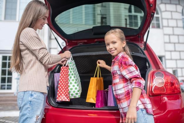 Mama i córka wyjmują torby na zakupy z bagażnika samochodu