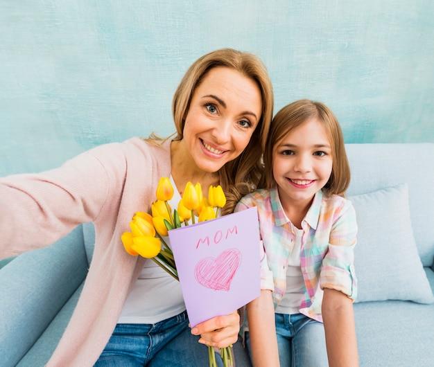Mama i córka z obecną uśmiechniętą bierze fotografią