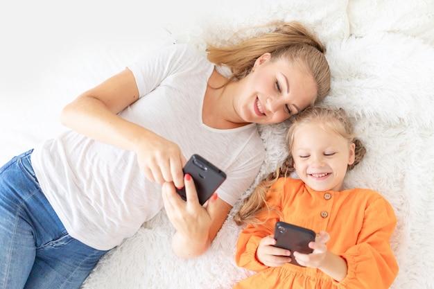 Mama i córka z telefonami komórkowymi leżą na łóżku w domu i robią sobie selfie lub rozmawiają przez łącze wideo