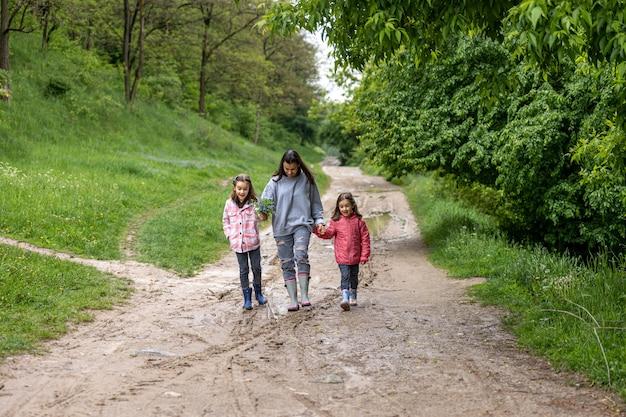 Mama i córki spacerują po lesie po deszczu wiosną w gumowych butach