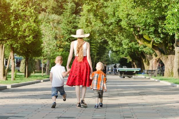 Mama i dwaj synowie spacerujący w parku, słoneczny dzień. widok z tyłu