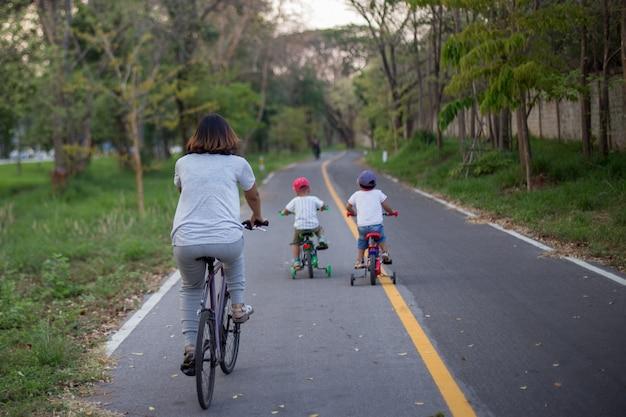 Mama i dwóch synów jeżdżą na rowerze na ścieżce rowerowej.