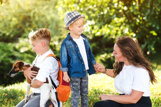 Mama i dzieci bawią się bawiąc się z psem na świeżym powietrzu. szczęśliwa rodzina korzystających w parku w słoneczny dzień. mały szczeniak jack russel terrier chodzenie z właścicielami. dzieci i pies to najlepsi przyjaciele.
