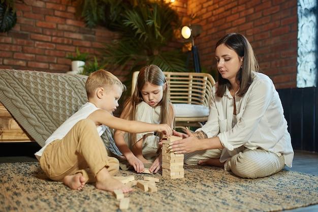 Mama i dzieci bawią się w wieżyczkę. kobieta, dziewczyna i chłopak grać w rodzinną grę logiczną. rodzinny dzień wolny
