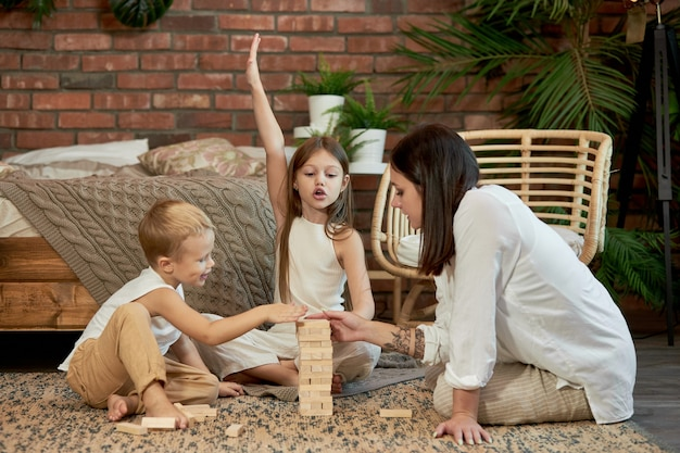 Mama i dzieci bawią się w wieżyczkę. kobieta, dziewczyna i chłopak, grają w rodzinną grę logiczną