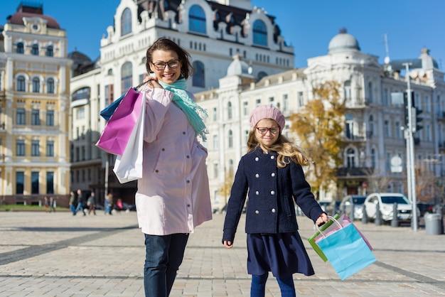 Mama i dzieci chętnie robią zakupy. trzymając torby na zakupy.
