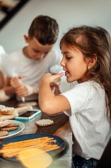 Mama i dzieci dekorują świąteczne pierniki w domu. chłopiec i dziewczynka malują kornetami