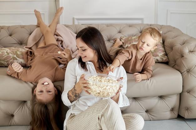 Mama i dzieci jedzą popcorn w domu w dzień wolny