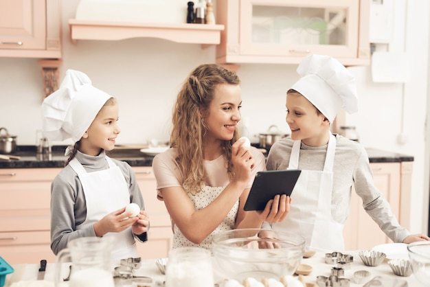 Mama i dzieci szukają przepisów kulinarnych. trzyma jajko.