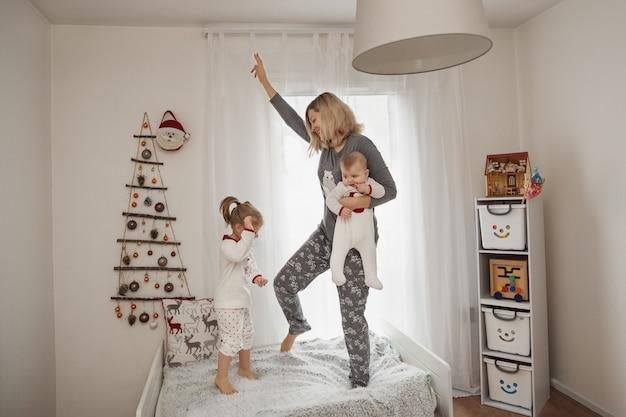 Mama i dzieci w piżamach skaczą na łóżku w pokoju dziecięcym