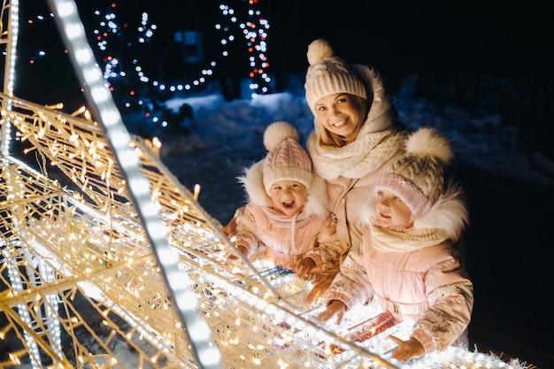 Mama i dzieci w wieczornym mieście z lampkami bożonarodzeniowymi w nocy