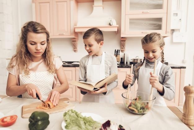 Mama i dzieciaki miesza domowej roboty sałatki przy kuchnią.