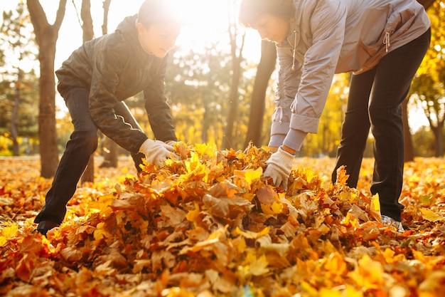 Mama i dziecko czyszczą opadłe liście w parku. kobieta i chłopiec zbierają liście. jesienny krajobraz. matka i syn, sprzątanie jesiennych liści na zewnątrz. działacze ochrony środowiska.