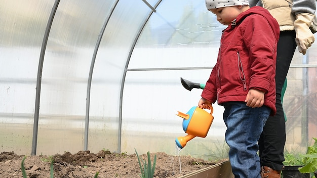 Mama i dziecko opiekują się roślinami w szklarni.