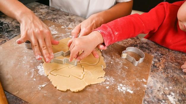 Mama i dziecko robią formę na ciasteczka noworoczne.