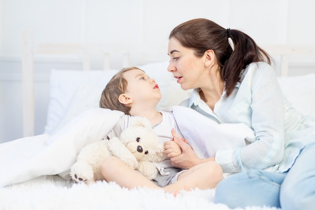 Mama i dziecko rozmawiają w domu na łóżku, pojęcie relacji między rodzicami a dziećmi