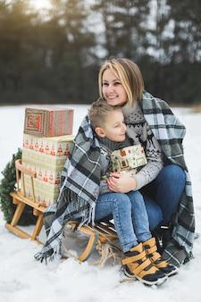 Mama i dziecko siedzą razem na drewnianych zdobionych saniach z prezentami świątecznymi