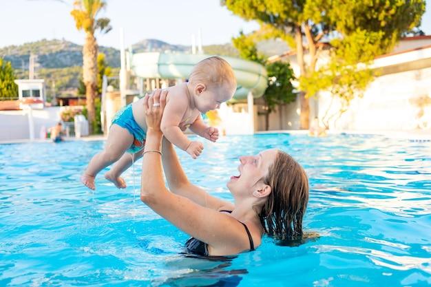 Mama i dziecko w basenie ze zjeżdżalniami latem bawią się pływając, podrzucając dziecko, relaksując się i spędzając czas z rodziną