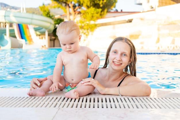 Mama i dziecko w basenie ze zjeżdżalniami latem świetnie się bawią pływając, relaksując się i spędzając czas z rodziną na wakacjach
