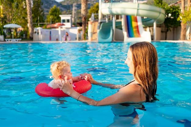 Mama i dziecko w dmuchanym kręgu w basenie ze zjeżdżalniami latem bawią się pływając, relaksując się i spędzając czas, mama uczy dziecko pływać