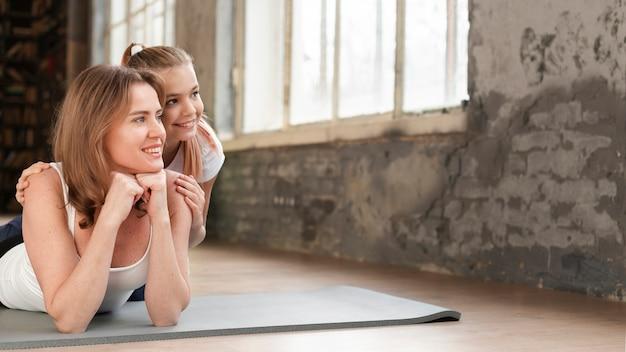 Mama i dziewczyna pozuje na matach do jogi, patrząc od hotelu