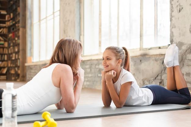 Mama i dziewczyna siedzi na macie patrząc na siebie