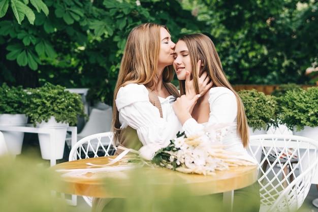 Mama i dziewczyna uśmiechają się i przytulają na letnim tarasie w kawiarni