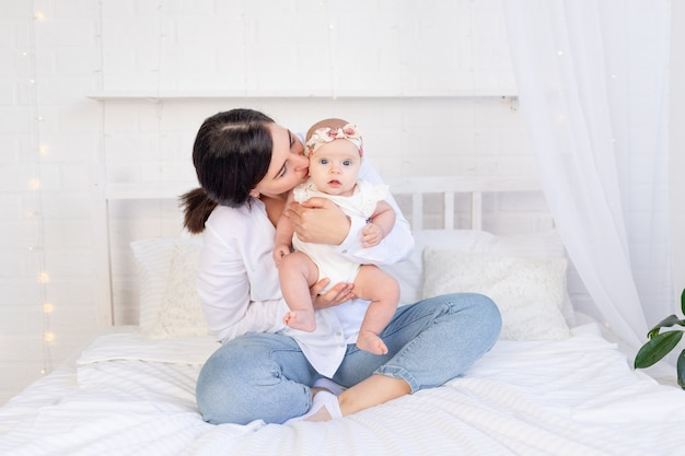 Mama i dziewczynka przytulają się i całują siedząc na białym bawełnianym łóżku w domu, matczyna miłość i troska