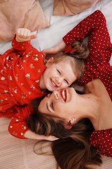 Mama i jej córeczka leżą na łóżku twarzą do siebie, są szczęśliwe