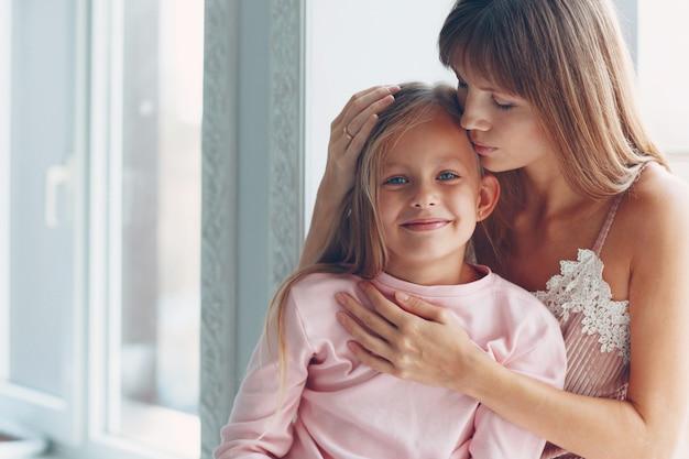 Mama i jej córeczka przytulają się i uśmiechają