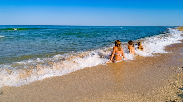 Mama i jej córki podziwiają widok na morze, siedząc na brzegu morza na falach