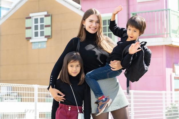Mama i jej dzieciaki robią z uśmiechem pamiątkowe zdjęcia