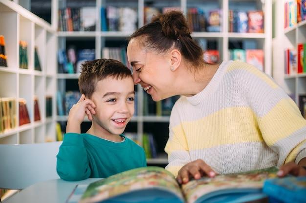Mama i jej małe dziecko, syn przedszkolaka, czytali razem książki dla dzieci